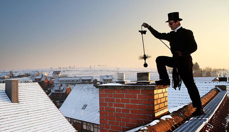 chimney sweep with stovepipe hat upon the roof